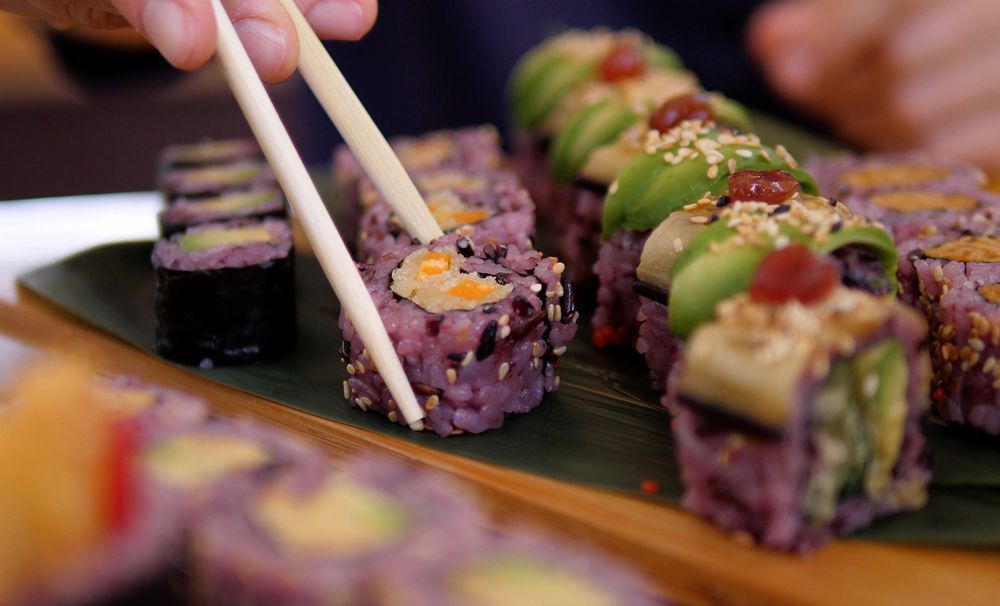 A vegan sushi picked up with chopsticks, in the works for Daikon Vegan Sushi & More on the westside.