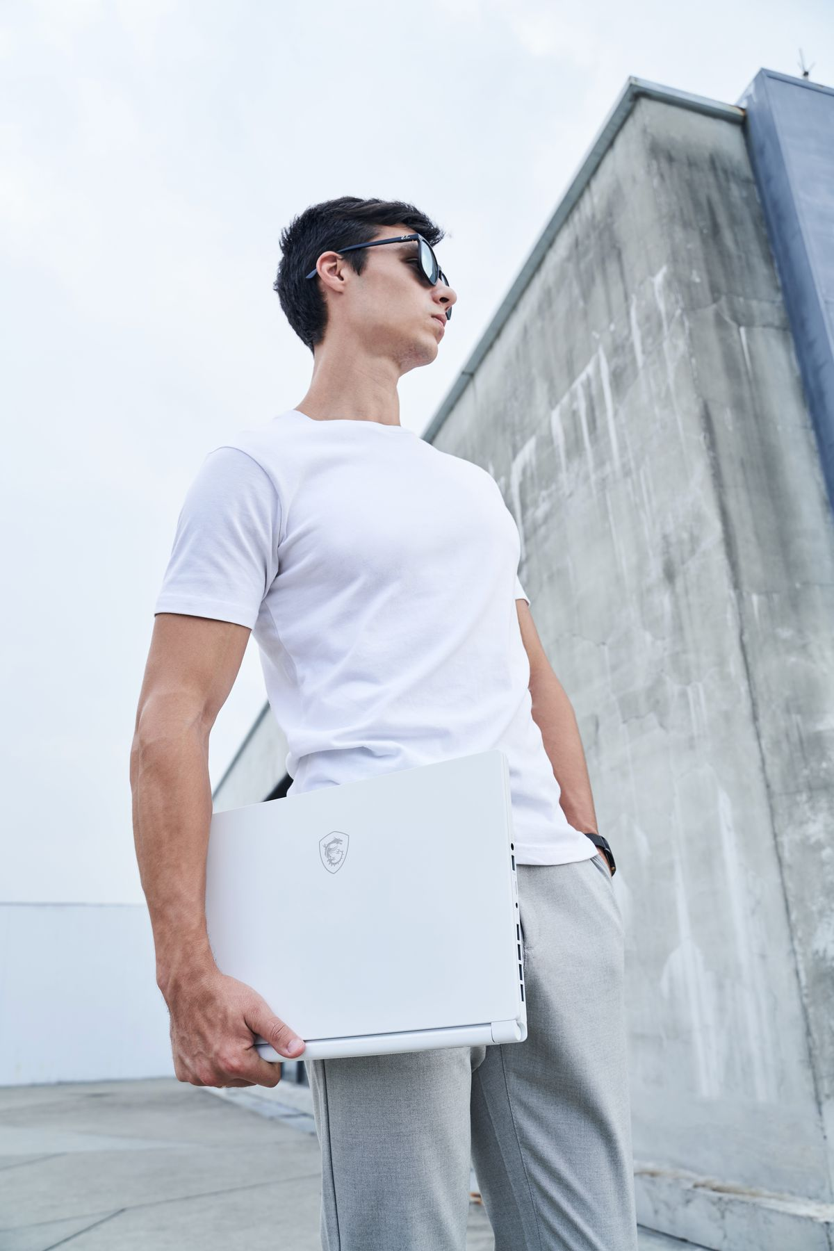 A user stands on the roof of a building wearing a white T-Shirt, sunglasses and sweatpants. They carry a white MSI Stealth 15M under their right arm while looking off to the left.