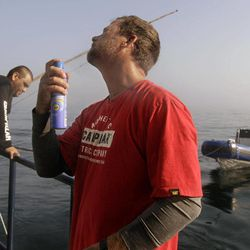 In this Sept. 7, 2012, photo, Ocearch expedition leader Chris Fischer applies sunscreen before leaving the ship to check chum locations for signs of great white shark activity in the Atlantic Ocean off the coast of Chatham, Mass. as deck hand Juan Valencia, left, monitors chumming activity off the back of the research vessel.  The Ocearch team baits the fish and leads them onto a lift, tagging and taking blood, tissue and semen samples up close from the world's most feared predator. The real-time satellite tag tracks the shark each time its dorsal fin breaks the surface, plotting its location on a map.