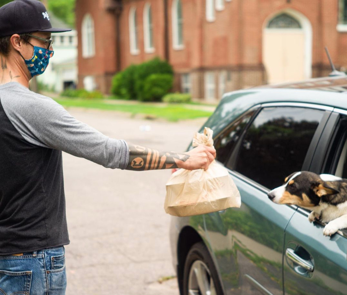 A man wearing a mask holding out takeout food to a dog in a car for curbside pickup.