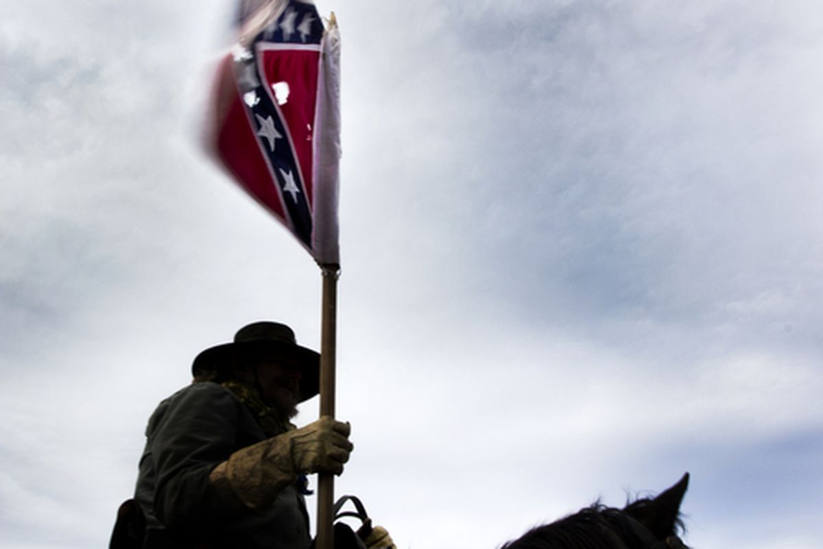 Man riding horse and carrying a Confederate flag