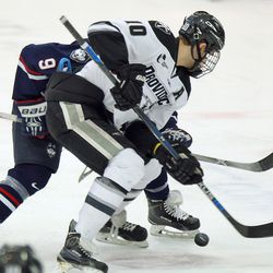 Providence's Mark Jankowski (10) shields UConn's Shawn Pauly (9) from the puck on a face-off.