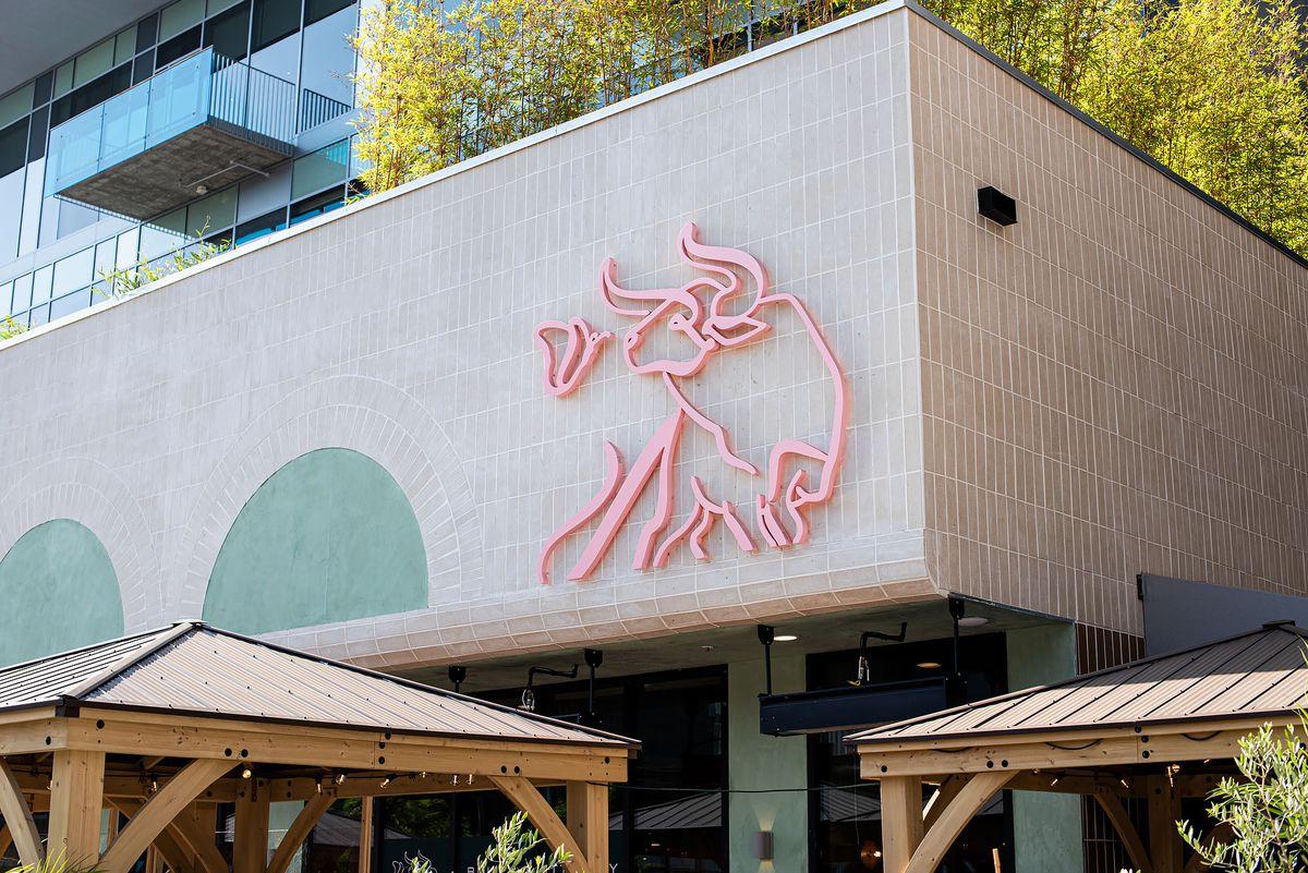 An exterior look at a corner restaurant with a light pink logo.