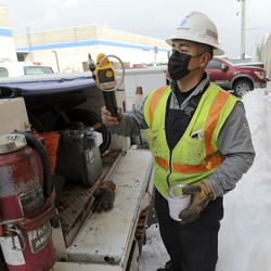 Dominion Energy utility worker Ramone Barrera puts tools away and grabs paint while replacing a gas meter in West Valley City on Wednesday, Feb. 17, 2021.