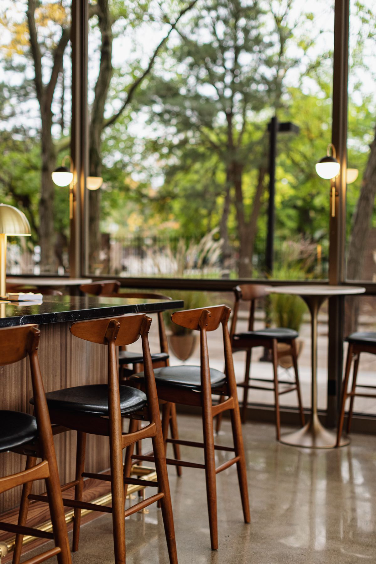 Mid-century style walnut bar chairs line a bar and match chairs surrounding circular two-top tables next to the windows. The chairs have a black seat.