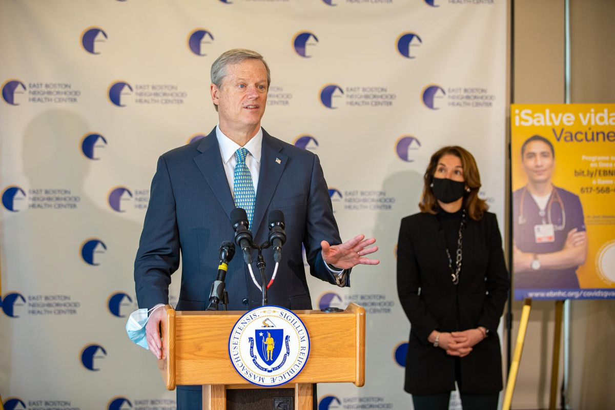 Massachusetts Governor Charlie Baker stands at a podium during a press briefing, while Lieutenant Governor Karyn Polito stands behind him wearing a mask
