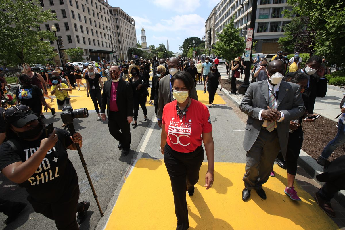 District of Columbia Mayor Muriel Bowser walks on the street leading to the White House after the words Black Lives Matter were painted in enormous bright yellow letters on the street by city workers and activists.