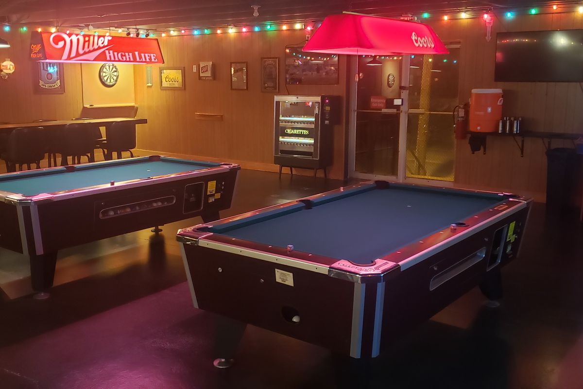 two pool tables, christmas lights hanging above, a cigarette machine in the back