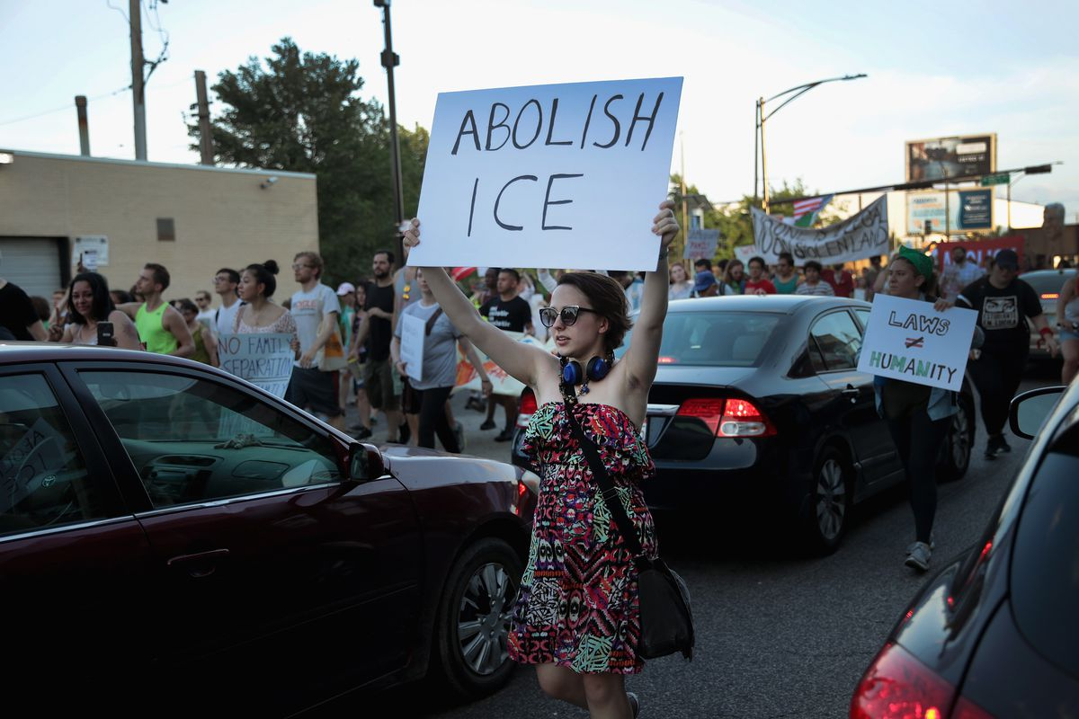 """A woman holds an """"abolish ICE"""" sign."""