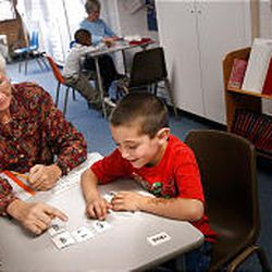 Volunteer Inga Chapman works with first-grader Tino Rodriguez in the hallway of the Guadalupe Schools.