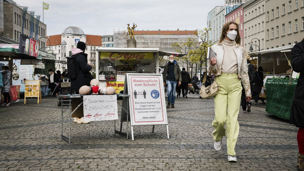 A woman in a mask and spring clothing walks through an outdoor market area, with vendors and crowds nearby.