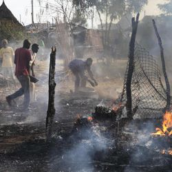 Residents try to extinguish fires still burning in the smouldering remains of a market in Rubkona near Bentiu in South Sudan Monday, April 23, 2012. A boy was killed and at least two people were wounded Monday when Sudanese aircraft bombed an area near the town of Bentiu in South Sudan, an official and witness said, increasing the threat of a full-scale war breaking out between the two nations.