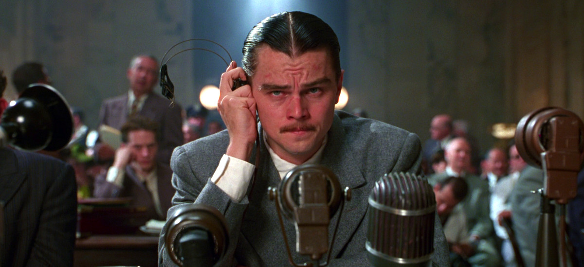 Howard Hughes (Leonardo DiCaprio) holds a listening device to his ear during a congressional hearing