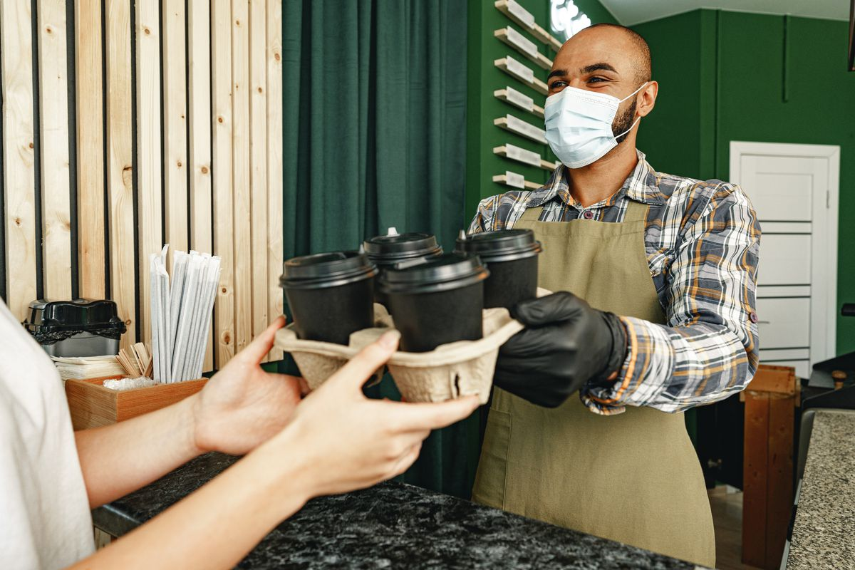 A masked barista handing a person to-go coffee