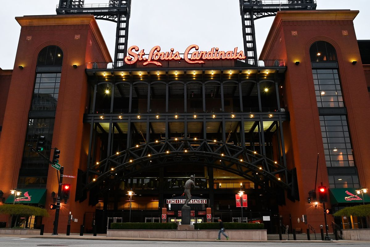 An exterior view of a Busch Stadium entrance, with two brick towers on each side of the picture, steel girders forming an arch over the entryway, and St. Louis Cardinals lit up in a cursive script at the top of the arch. There is a statue of an unknown Cardinals player in front of the stadium.