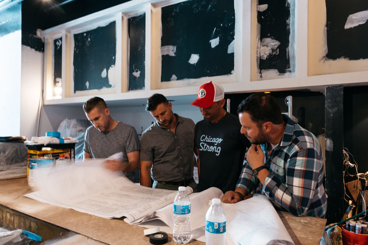 Four people inside an unfinished bar space looking over plans.