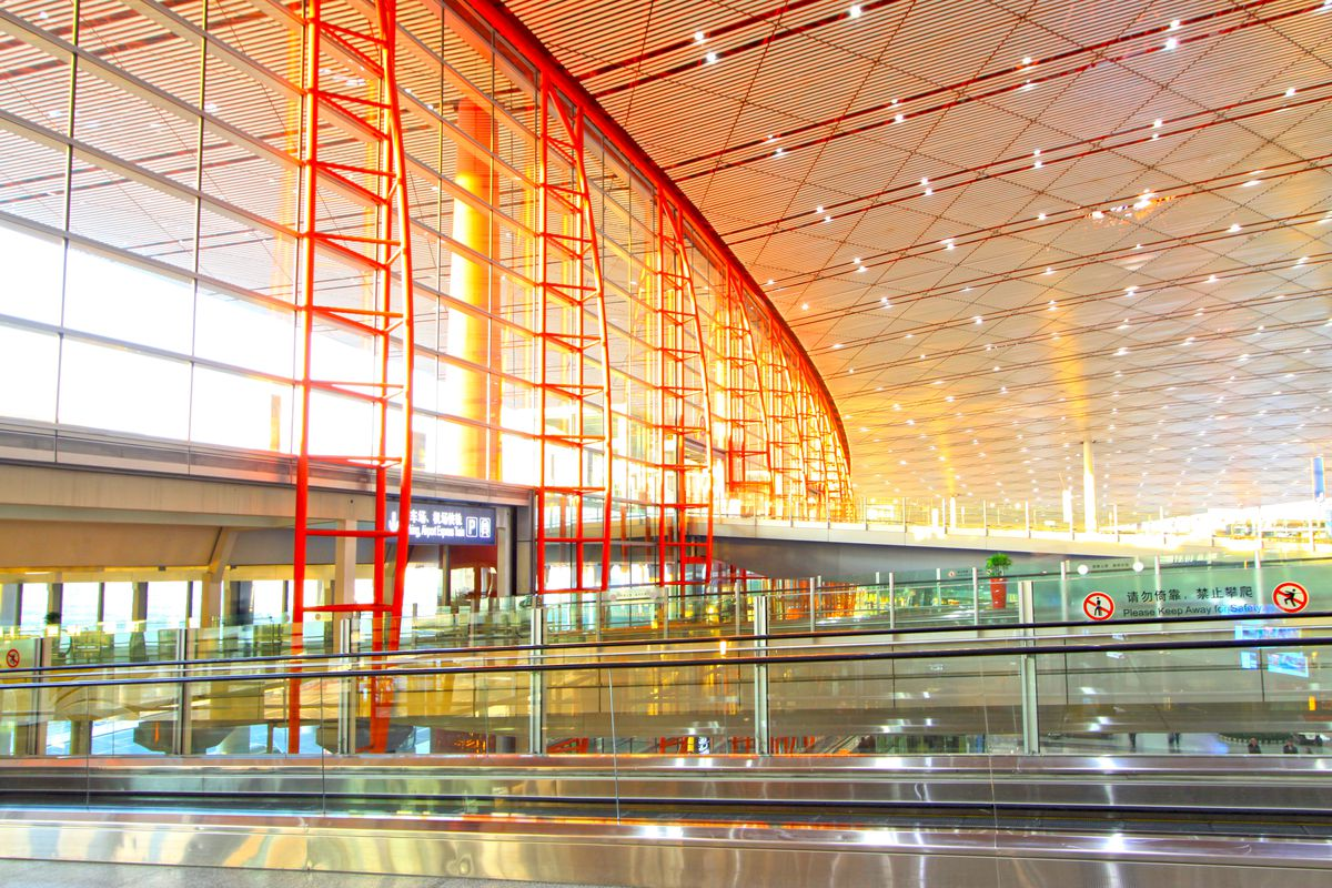 The interior of Beijing Capital International Airport. The walls are glass and both the walls and ceiling have red and orange beams running across them.