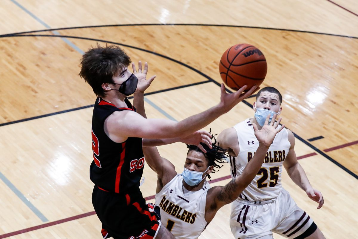 Maine South's Sean Gallery (12) takes the ball to the basket over Loyola's Perrion McClinton (1) and Vaughn Pemberton (25).