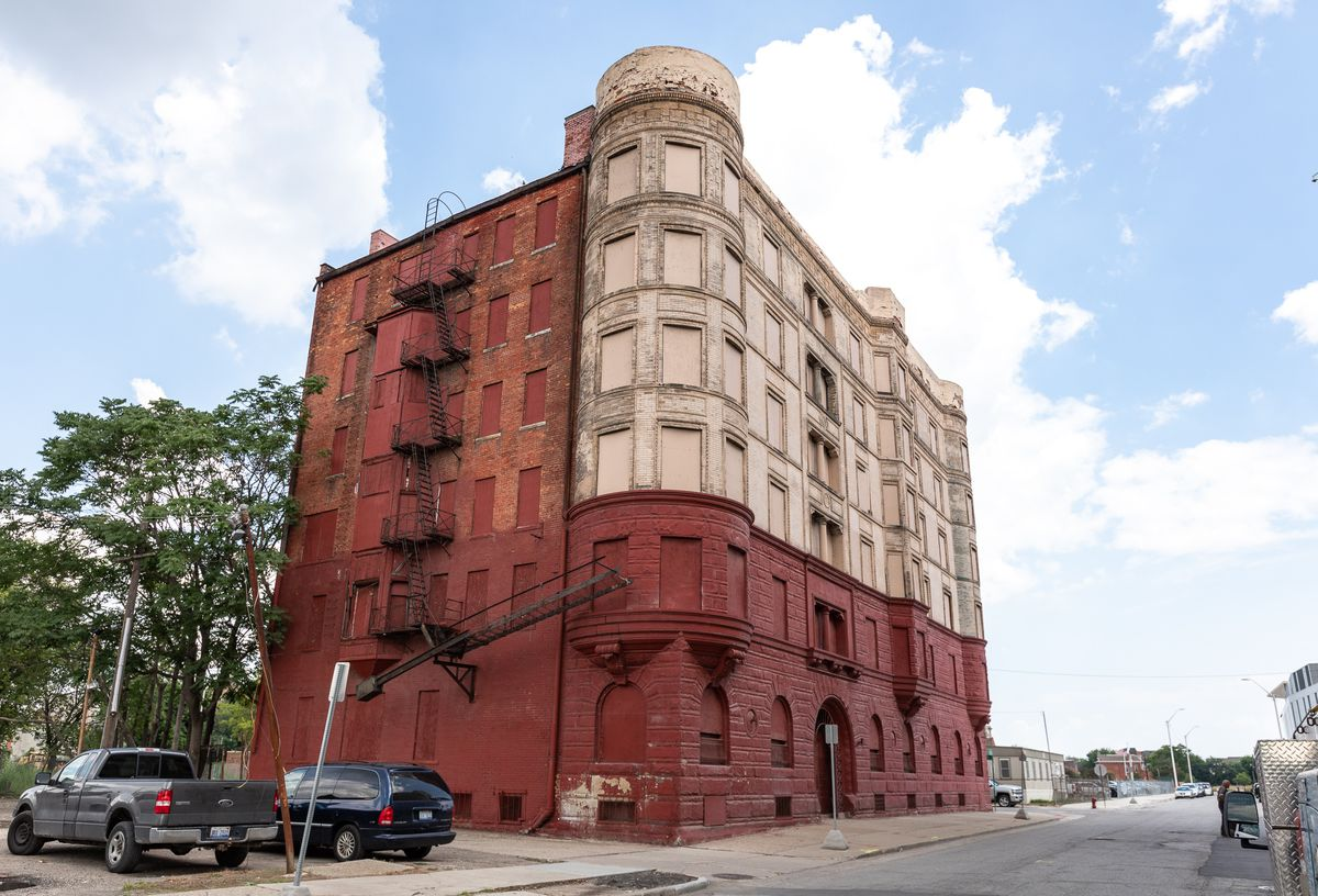 A multi-story boarded up building whose bricks have been painted red and white.