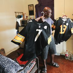 Bryan Coward show off his Pittsburgh Steelers jerseys at his tiny home at Community First! Village in Austin, Texas, on Tuesday, Oct. 20, 2020.