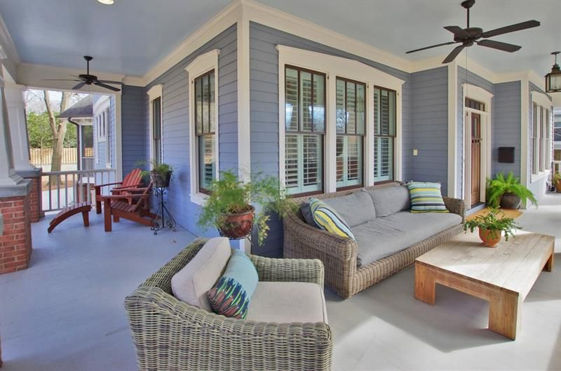 A blue porch with many ceiling fans and windows, plus beige couches.
