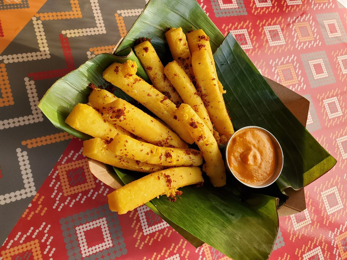 Turmeric yellow chickpea tofu fries rest on a green banana leaf at Thamee