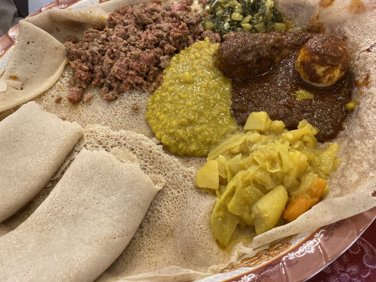 A variety of stews on injera, with more flatbread rolled up to the side