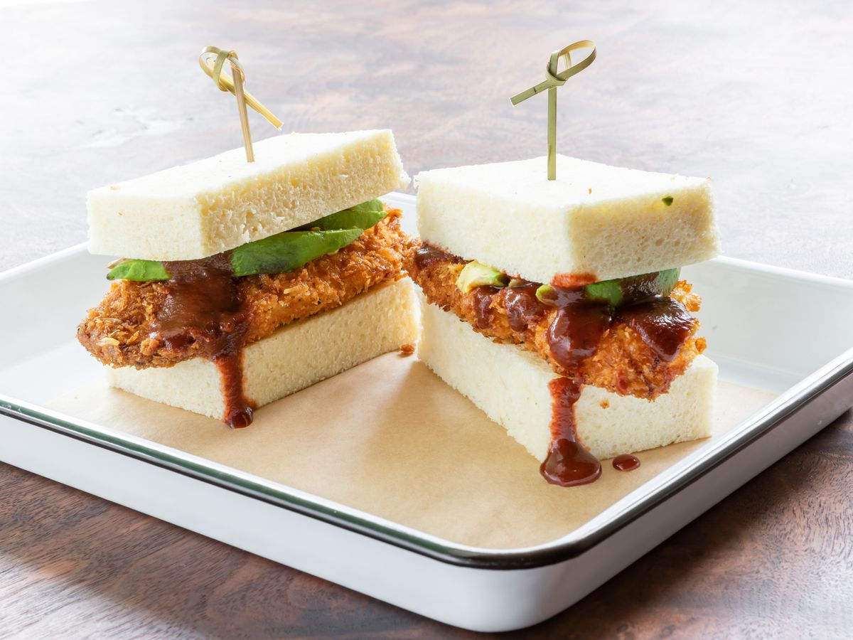 A sandwich of fried chicken on white milk bread, dripping with chamoy sauce
