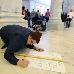 Gregory Leon Gates modifies his sign to criticize President Barack Obama as Utahns for the Medicaid Expansion held a rally in the rotunda at the state Capitol on Wednesday, Nov. 20, 2013, in Salt Lake City. The group rallied to show Gov. Gary Herbert he has support if he decides to expand Medicaid.