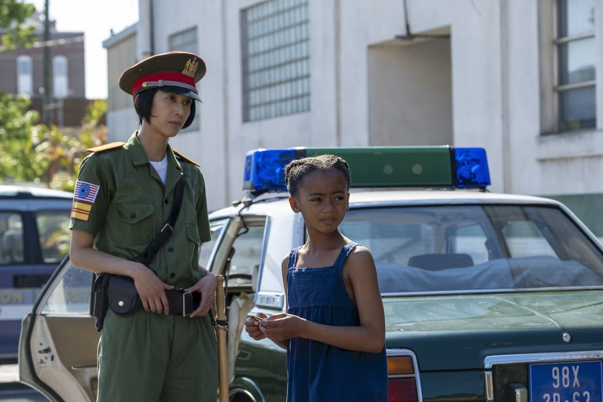 a vietnamese cop and a young angela stand in front of a green police car