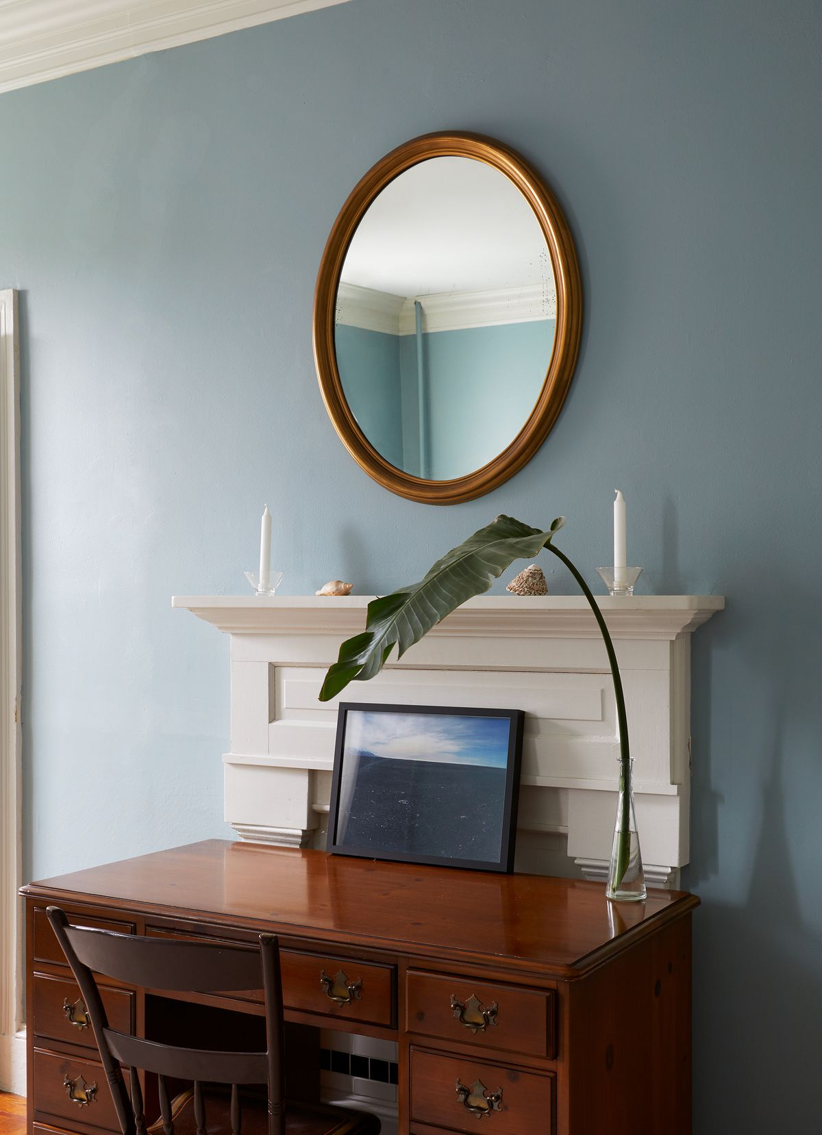 A part of a room. There is a wooden desk with a chair. A plant in a glass vase is on top of the desk. There is a fireplace against the wall. Above the fireplace is an oval mirror. The wall is painted light blue.