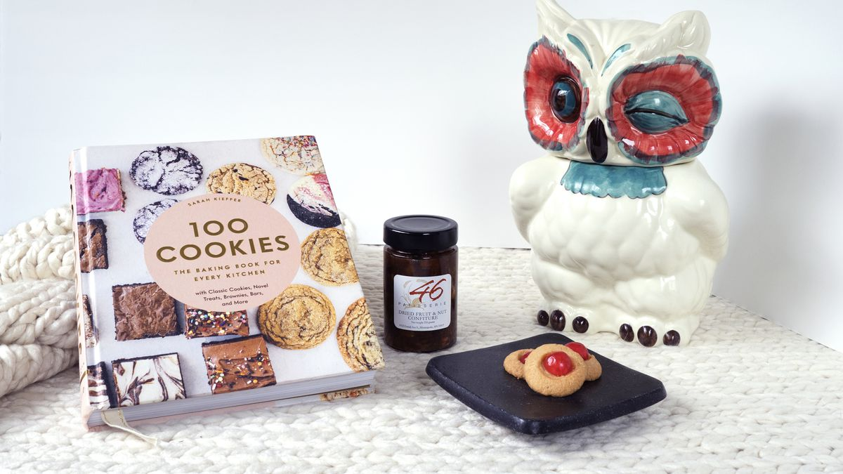 100 Cookies by Sarah Kieffer cookbook, a small plate of cookies with red candies, a jar of jam, and an owl cookie jar