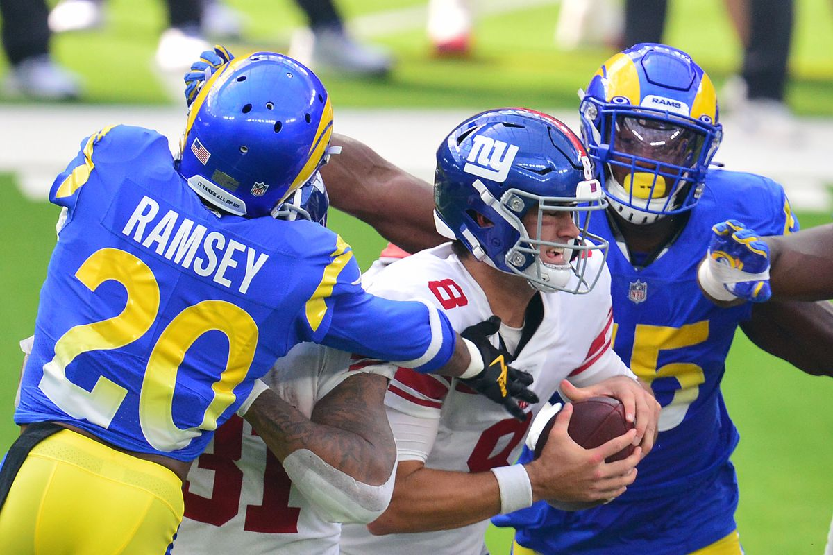 New York Giants quarterback Daniel Jones (8) is brought down by Los Angeles Rams cornerback Jalen Ramsey (20) and center Coleman Shelton (65) during the first half at SoFi Stadium.