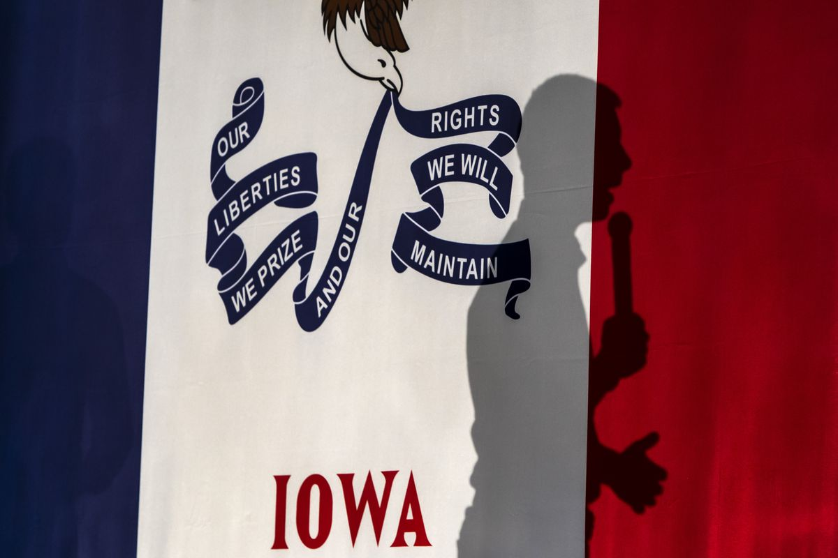 Only the shadow of Buttigieg can be seen as he delivers a speech in front of Iowa state flag.