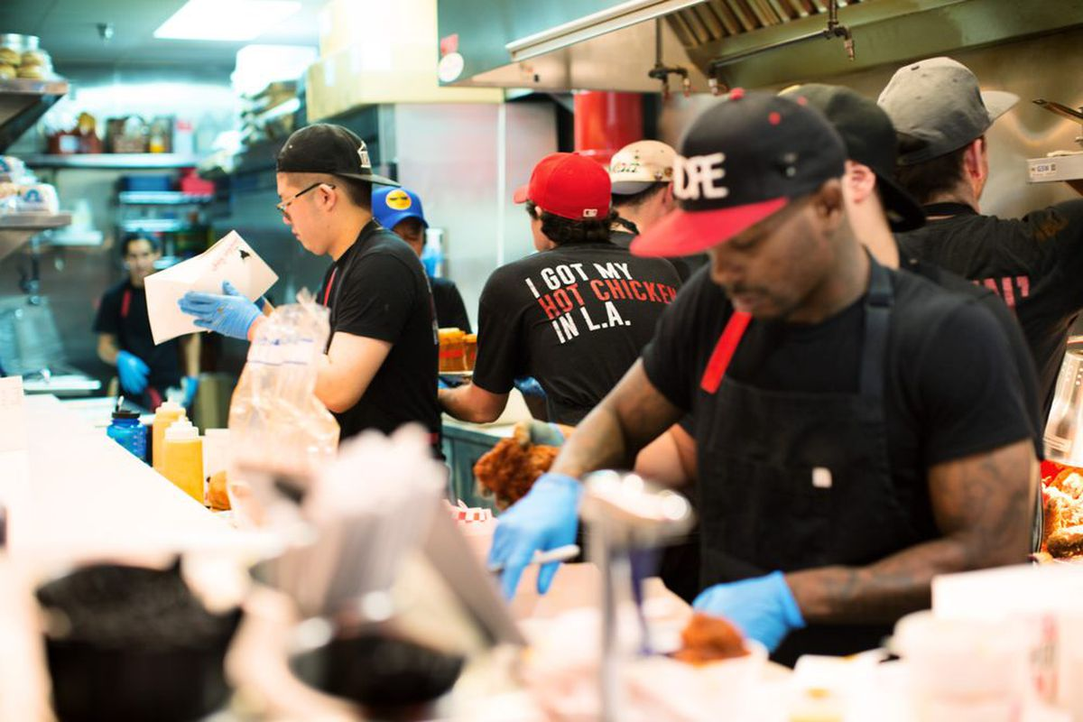 A close group of restaurant employees work together inside a small kitchen selling chicken.