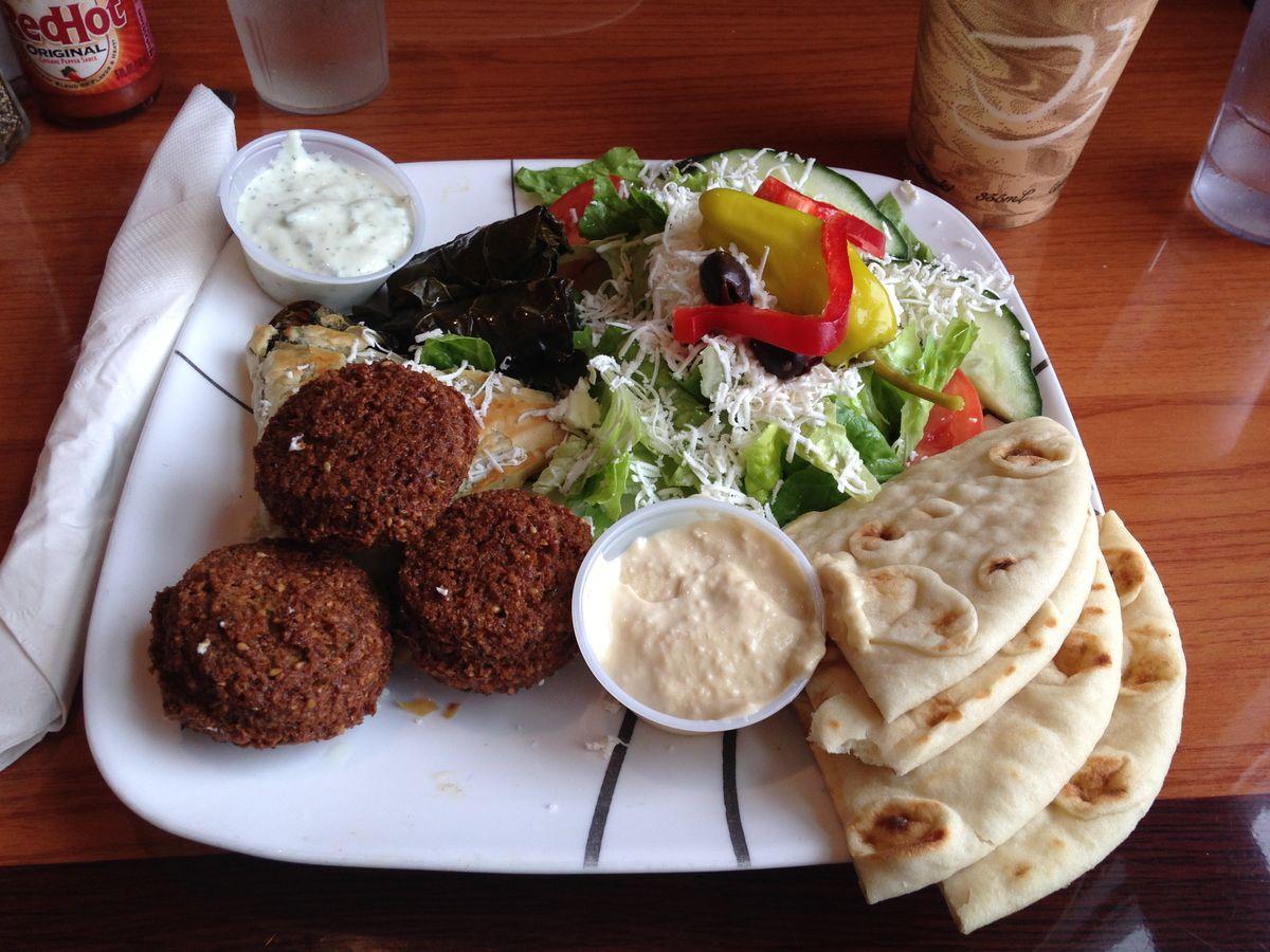 A platter of falafel, salad, pita, and dips.