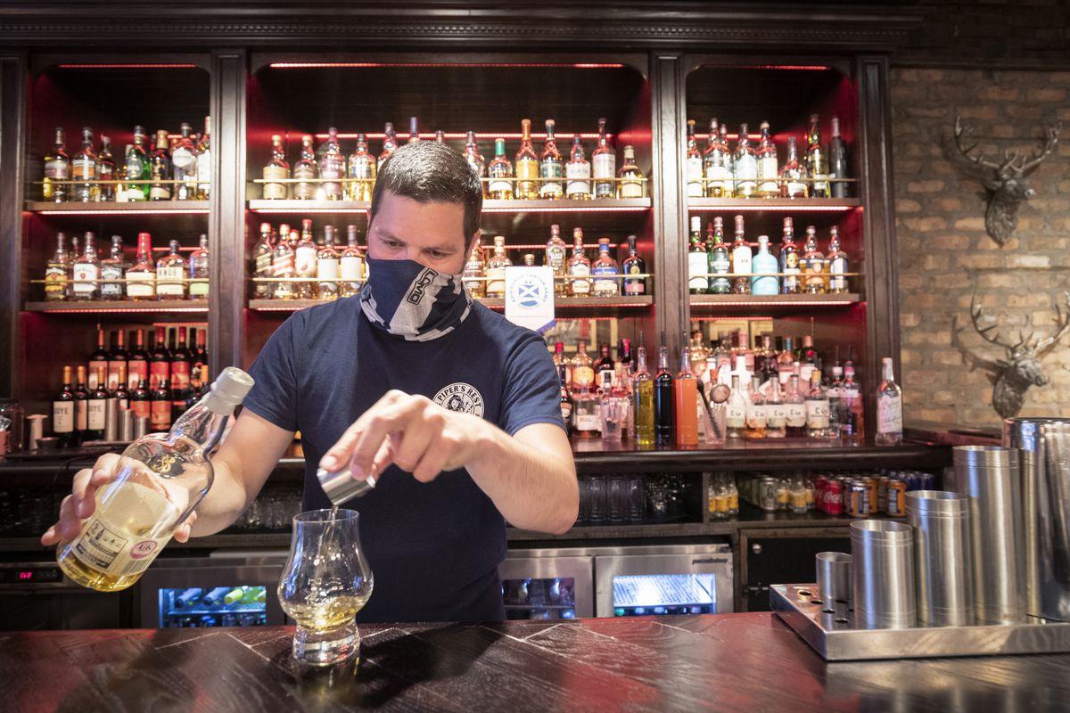 A barman in a mask serves a whisky at a pub