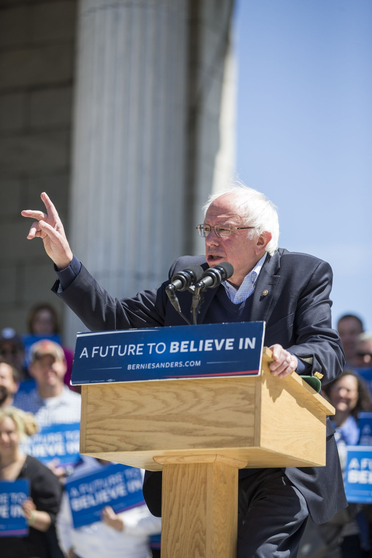 Bernie Sanders wearing a suit a rally