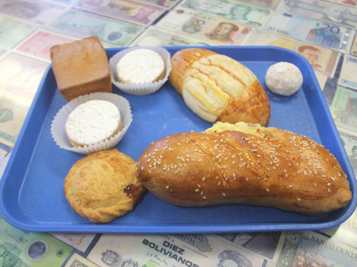 A blue tray filled with puffy brown pastries and breads.