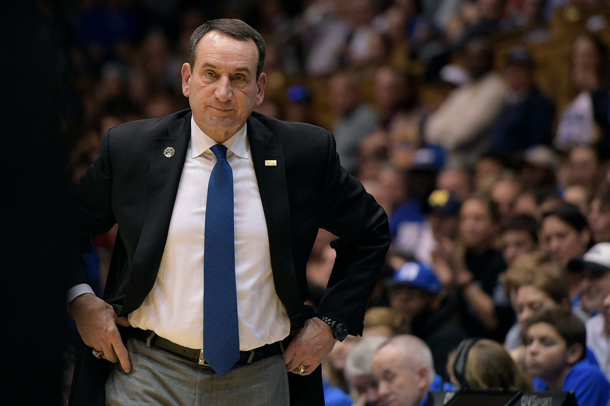 Mike Krzyzewski stands by the court with his hands on his hips
