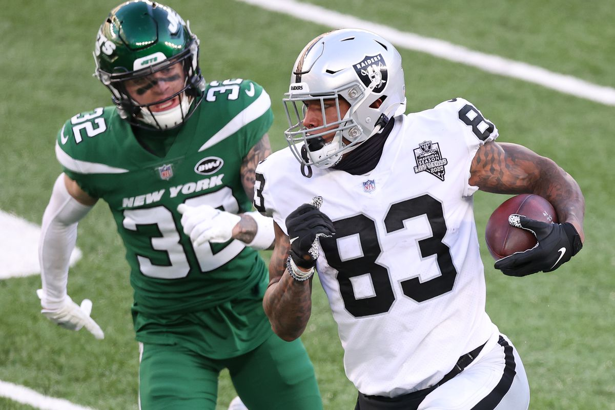 Darren Waller of the Las Vegas Raiders carries the ball as Ashtyn Davis of the New York Jets gives chase during the second half at MetLife Stadium on December 06, 2020 in East Rutherford, New Jersey.