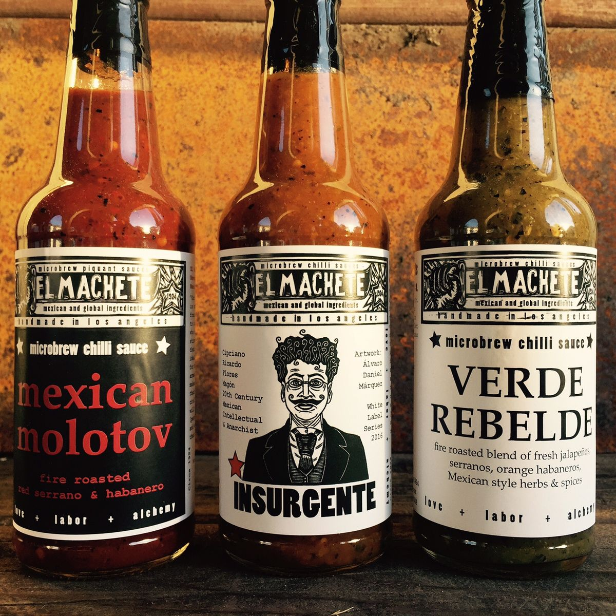 Three bottles of hot sauce lined up.