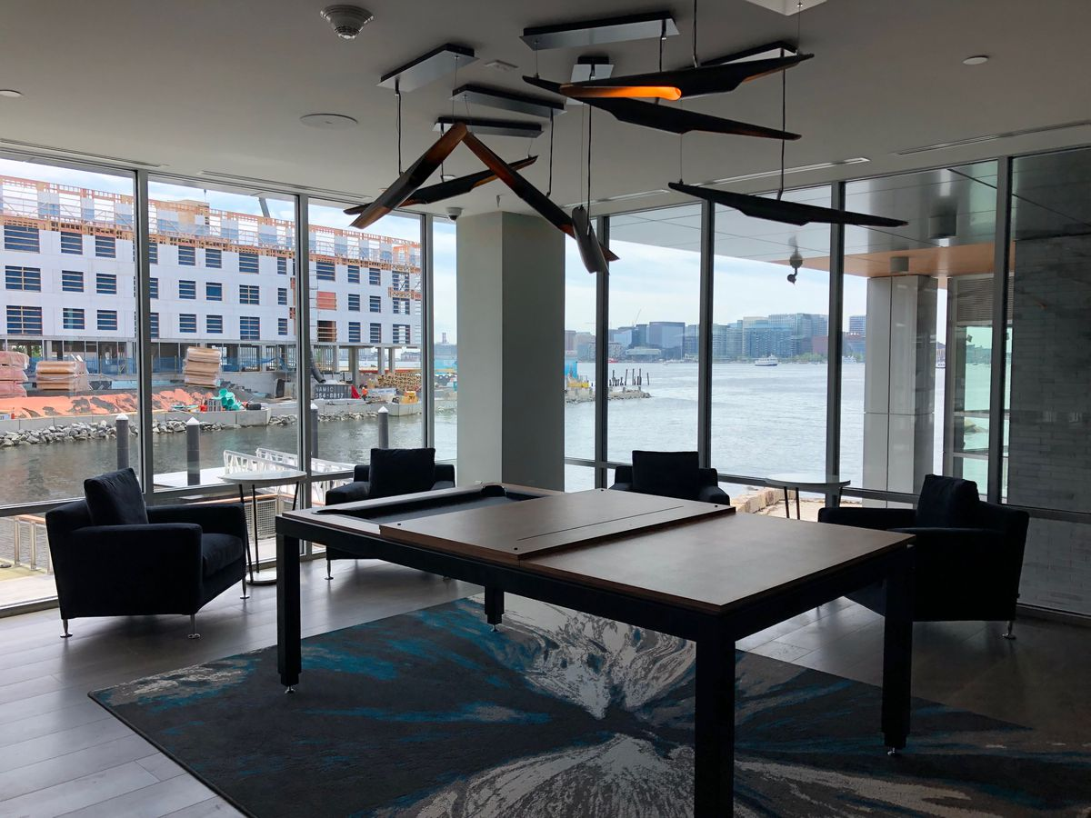 A conference room with a table, chairs, and windows overlooking a harbor.