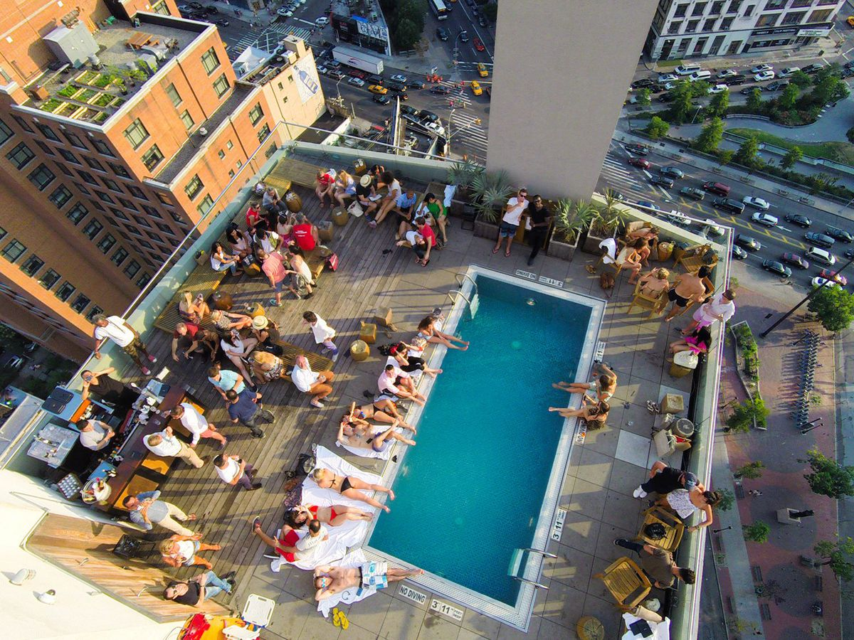 An aerial photograph of a hotel pool, whose water is dark blue and surrounded by reclining people with their feet in the water