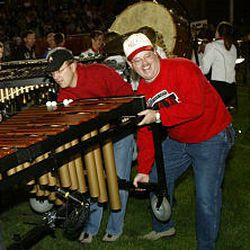 Band dads Brian Jensen, left, and Bart Reeset lift band equipment off of trailers and onto the football field.