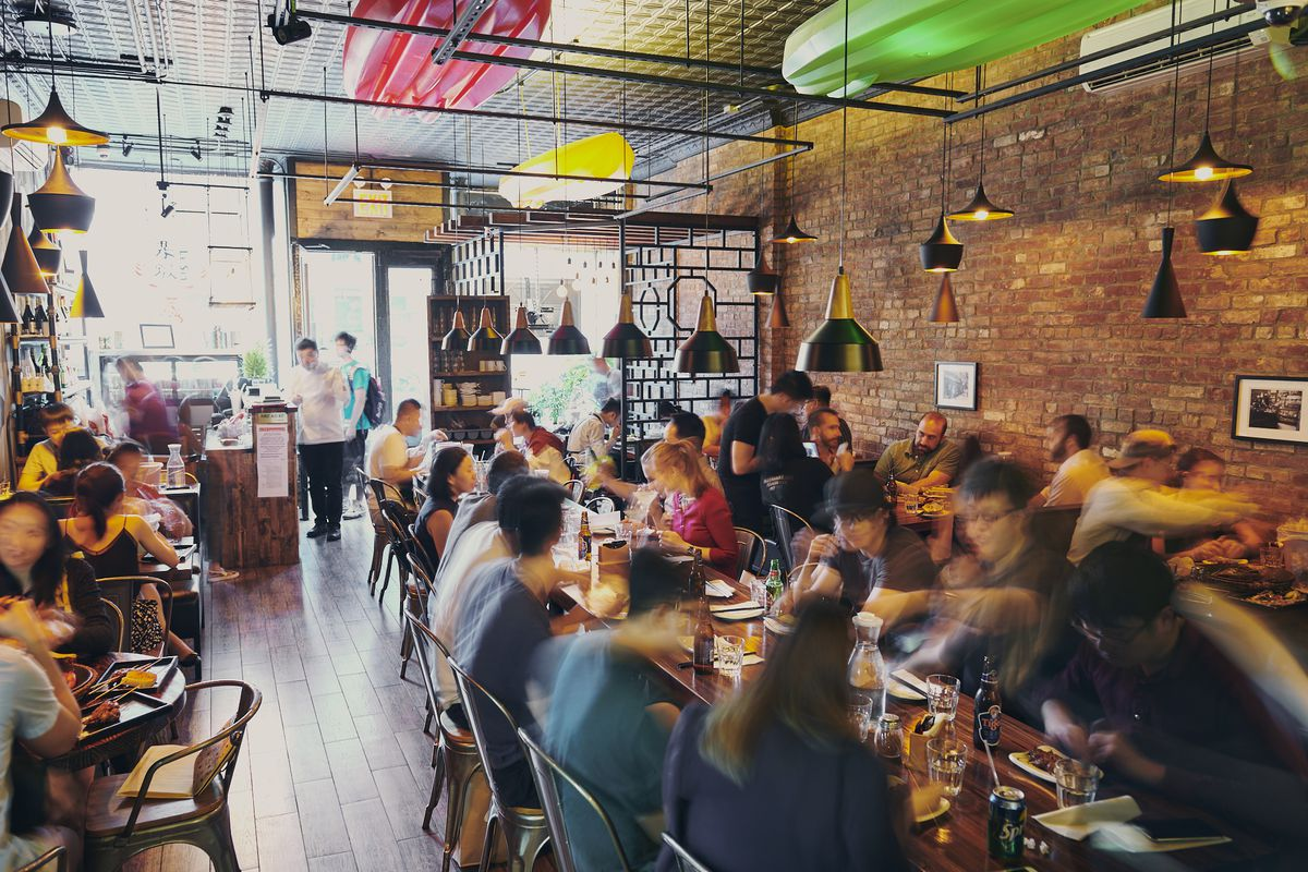 Le Sia's busy dining room full of customers and an exposed brick wall