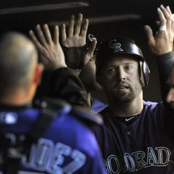 Colorado Rockies' Michael Cuddyer is congratulated by teammates after scoring a run on a Tyler Colvin RBI double off San Diego Padres startingpitcher Cory Luebke during the second inning of a baseball game, Monday, April 16, 2012, in Denver.