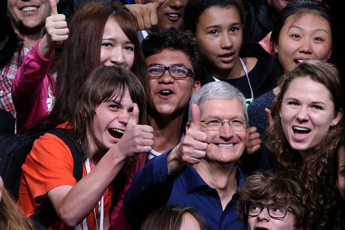 Apple CEO Tim Cook with some young people who probably don't buy music from the iTunes Store.