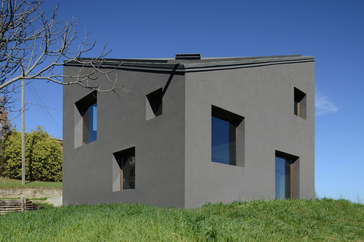 A blocky structure with dark grey walls and square windows sits on a grassy site.