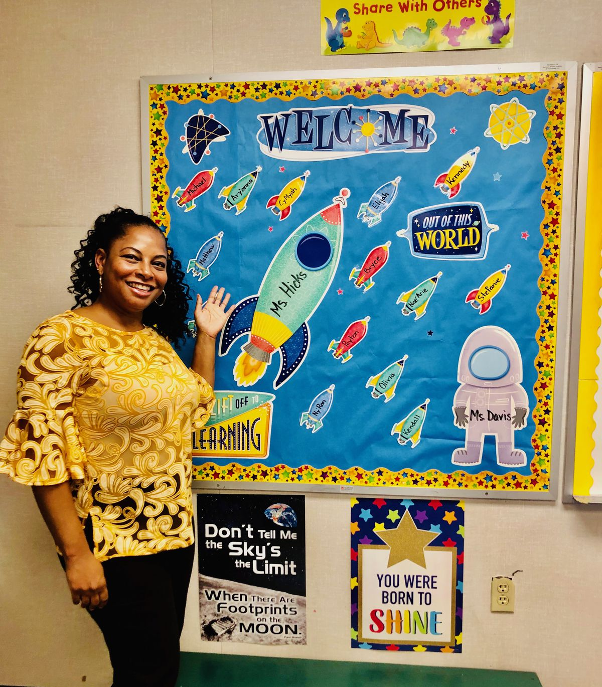 A teacher stands in front of a bulletin board on the first day of school 2020